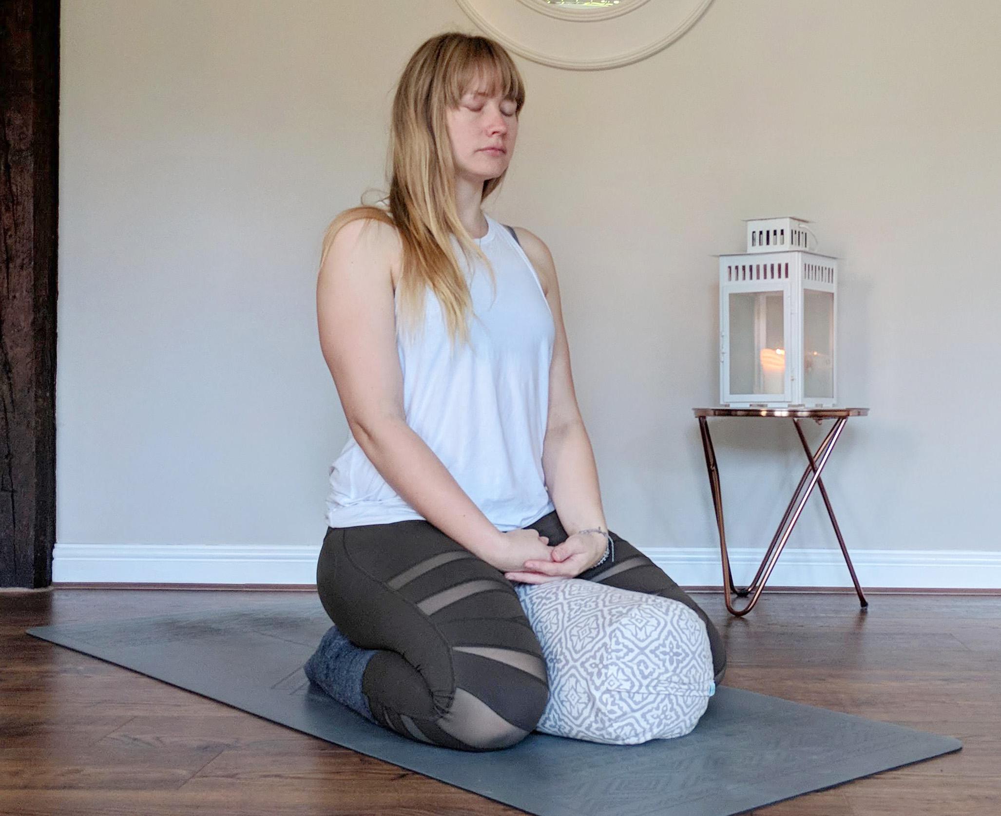 kneeling astride a bolster for meditation