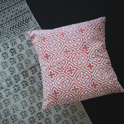 hand block printed cushion in coral pink laid on top of hand block printed rugYogipod