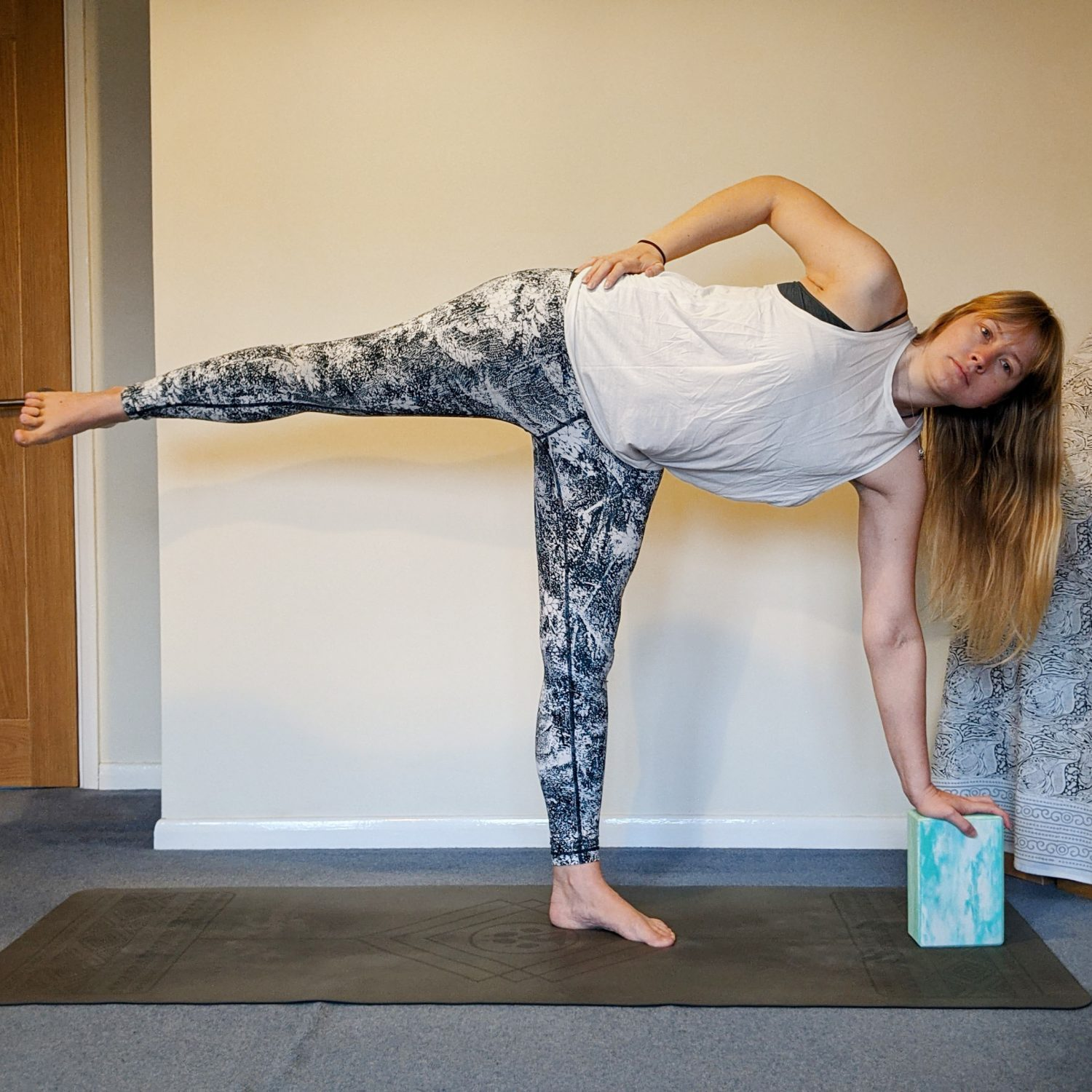 half moon pose with a block under the hand and the hand to the hip