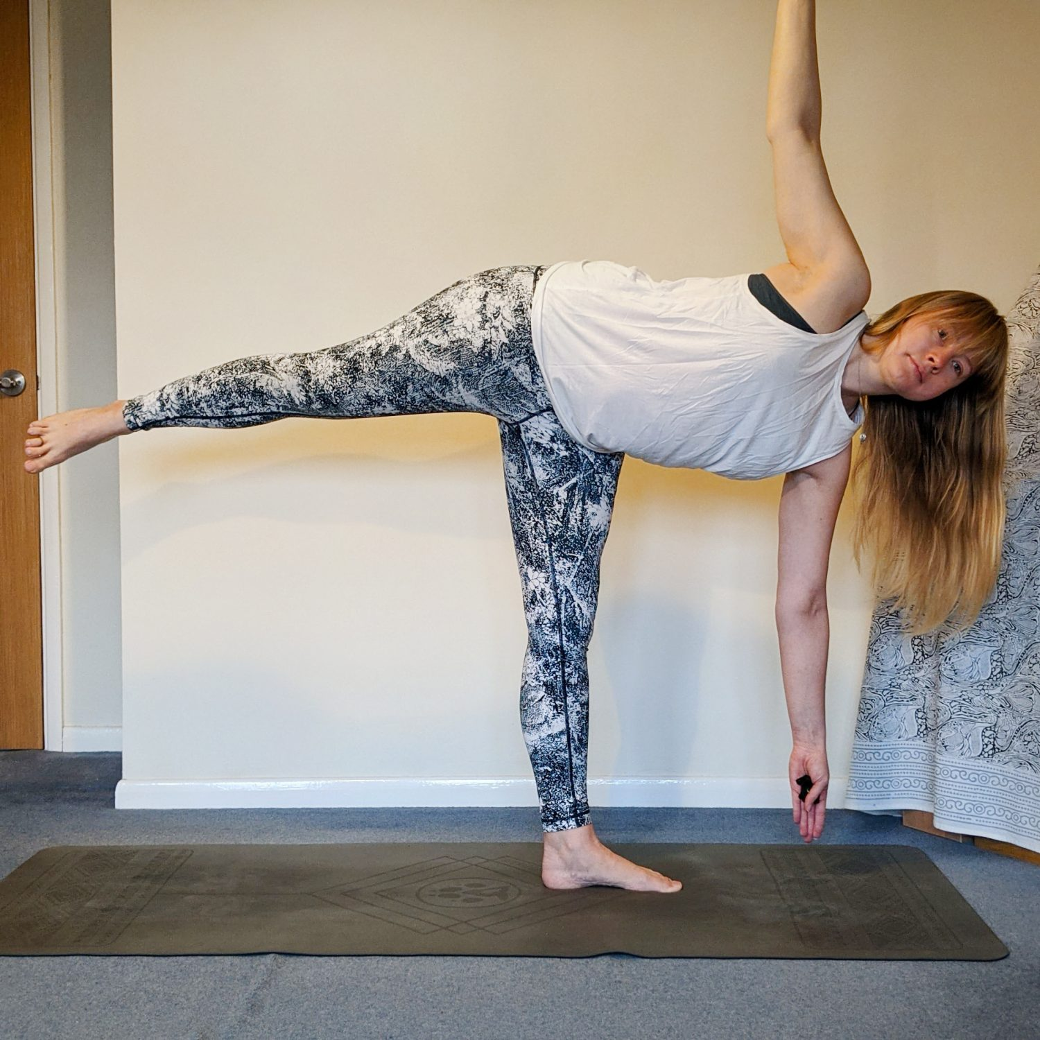 half moon pose with arm to ceiling and leg floating to the side