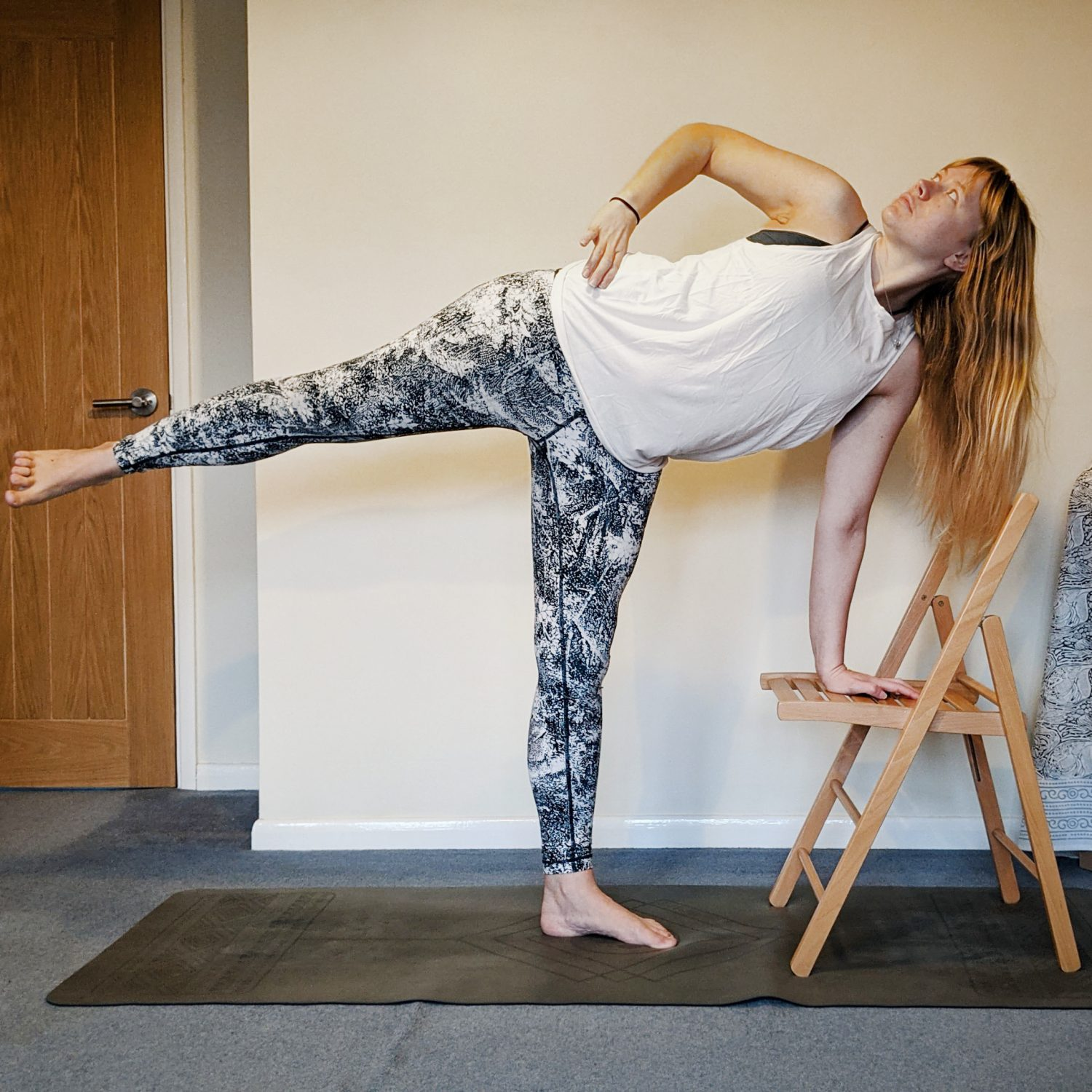 half moon pose with one hand to a chair to help balance
