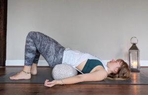 restorative bridge pose with a Yogiod bolster under the hips
