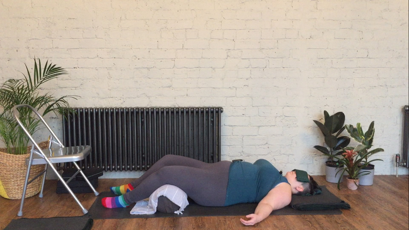 Sarah lays on the ground with a yoga bolster propped under her knees, a blanket under head and an eye pillow over the eyes for savasana