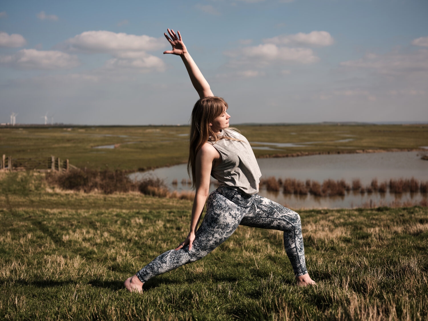 georgie does yoga in front of a lake at elmley nature reserve - private yoga classes Yogipod
